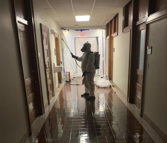 technician in PPE spraying disinfectant along wall