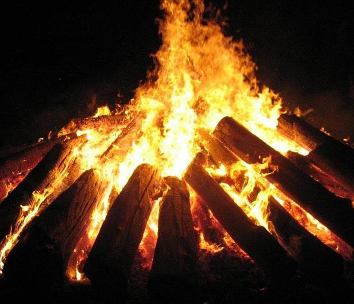 Eye level view of someone sitting around a bonfire during the night