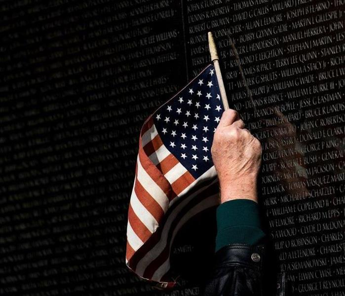 The American flag being risen to Veteran names written on a memorial site.