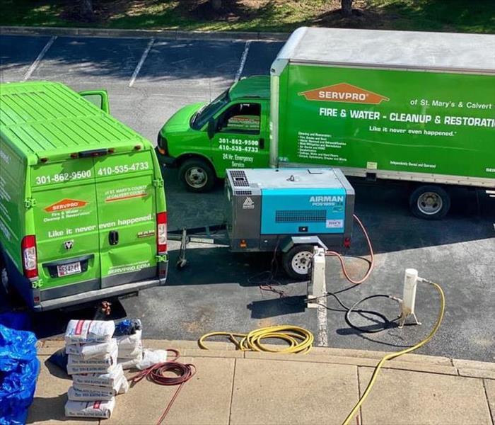 green SERVPRO trucks at a job