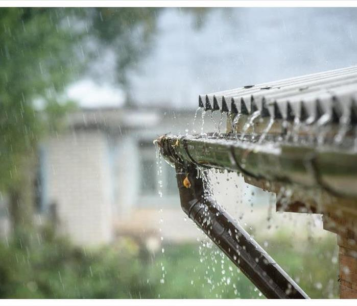 Rainwater dripping off a roof during a rain shower