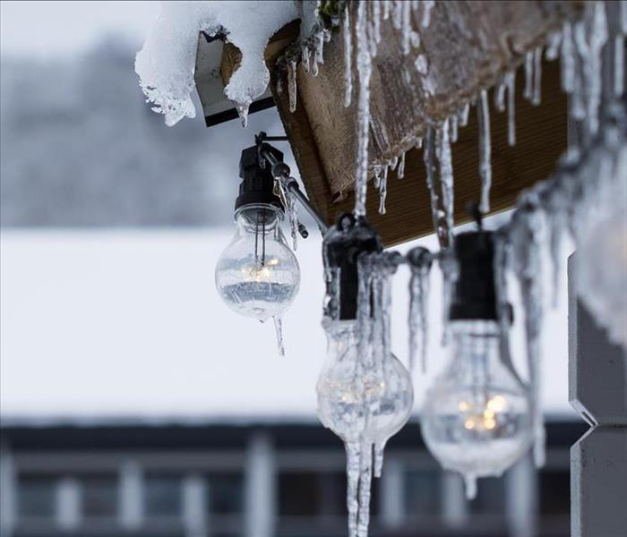 icicles hanging down from a homes with big Christmas lights and mountain back ground